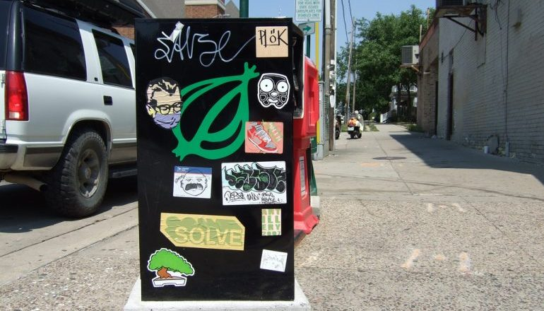 Metal news box on the side of the road covered in stickers, including the logo of The Onion