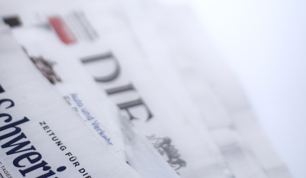 Close up picture of a stack of newspapers.