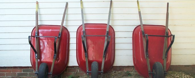 Three red wheelbarrows leaning against the wall of a house.
