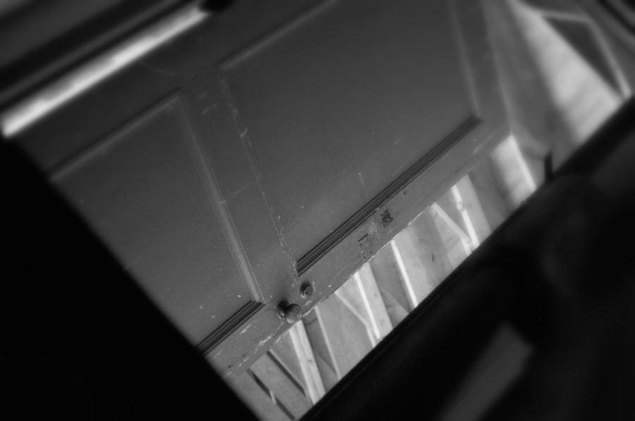 Black and white angled picture of a door ajar