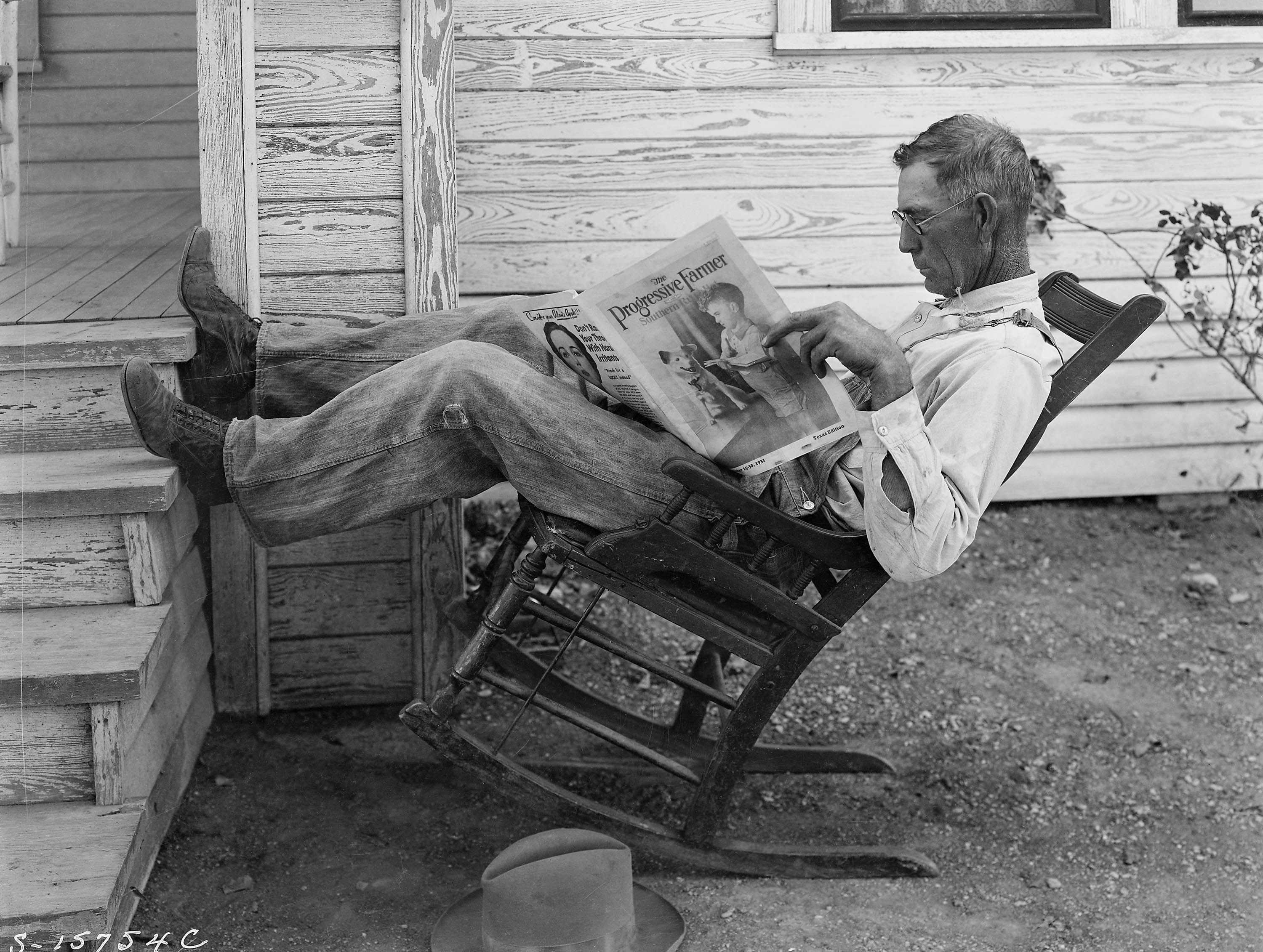 Old photograph of a man sitting on a reclining chair reading a newspaper