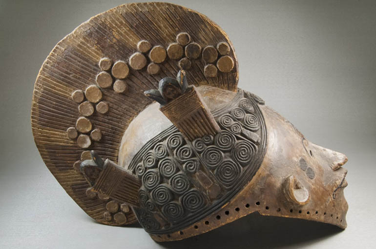 Picture of an old artifact that resembles a mas with a helmet.