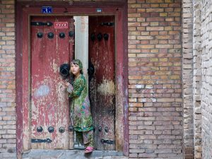Picture of a woman leaning against a worn, red wood door.