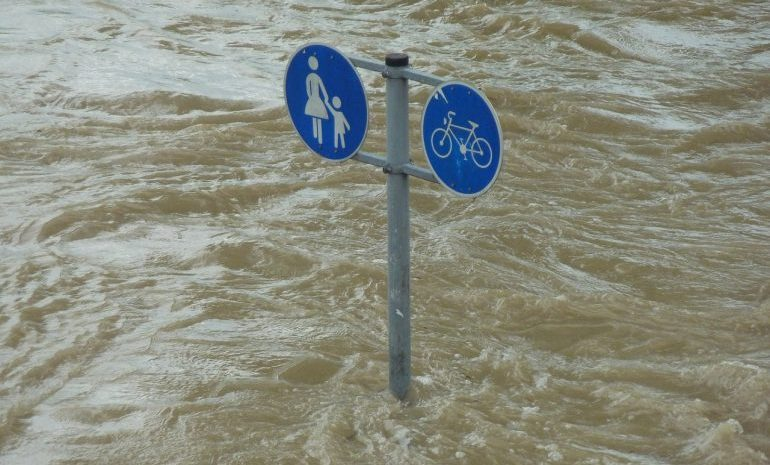 Picture of a street sign in the middle of a flood