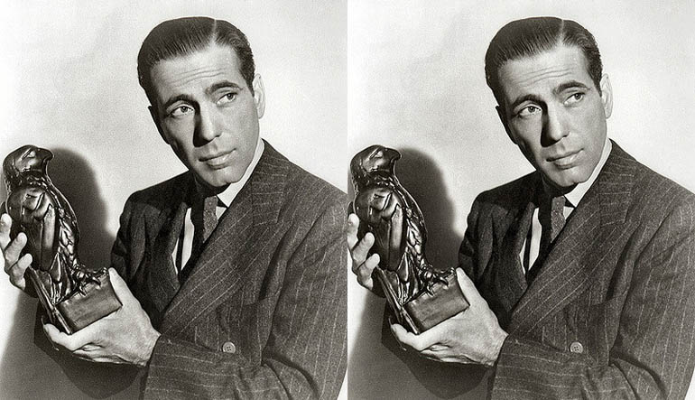Picture of a man holding up a small bird statue