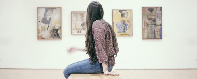 woman sitting on floor in art gallery