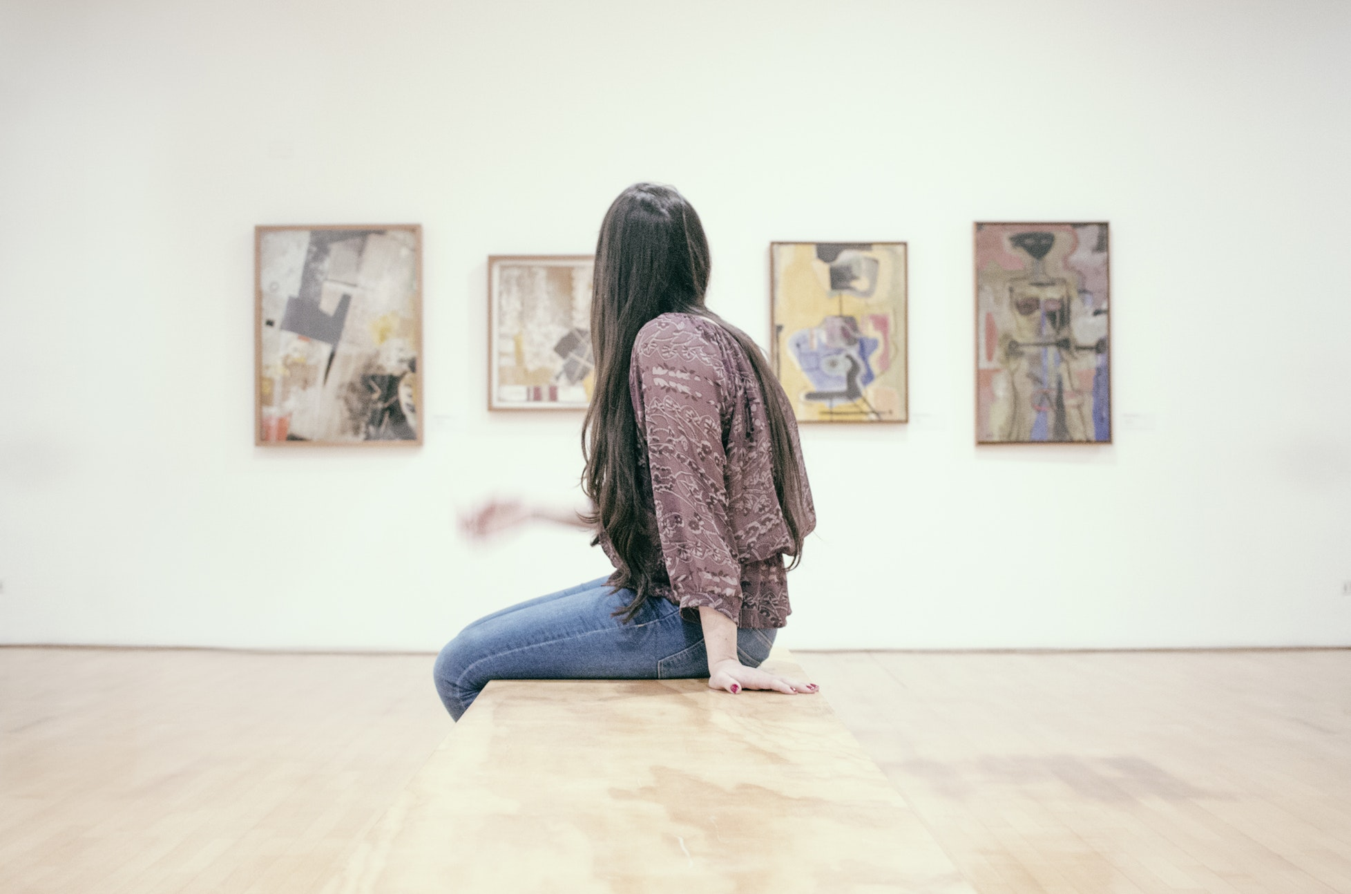woman sitting on a bench in an art gallery