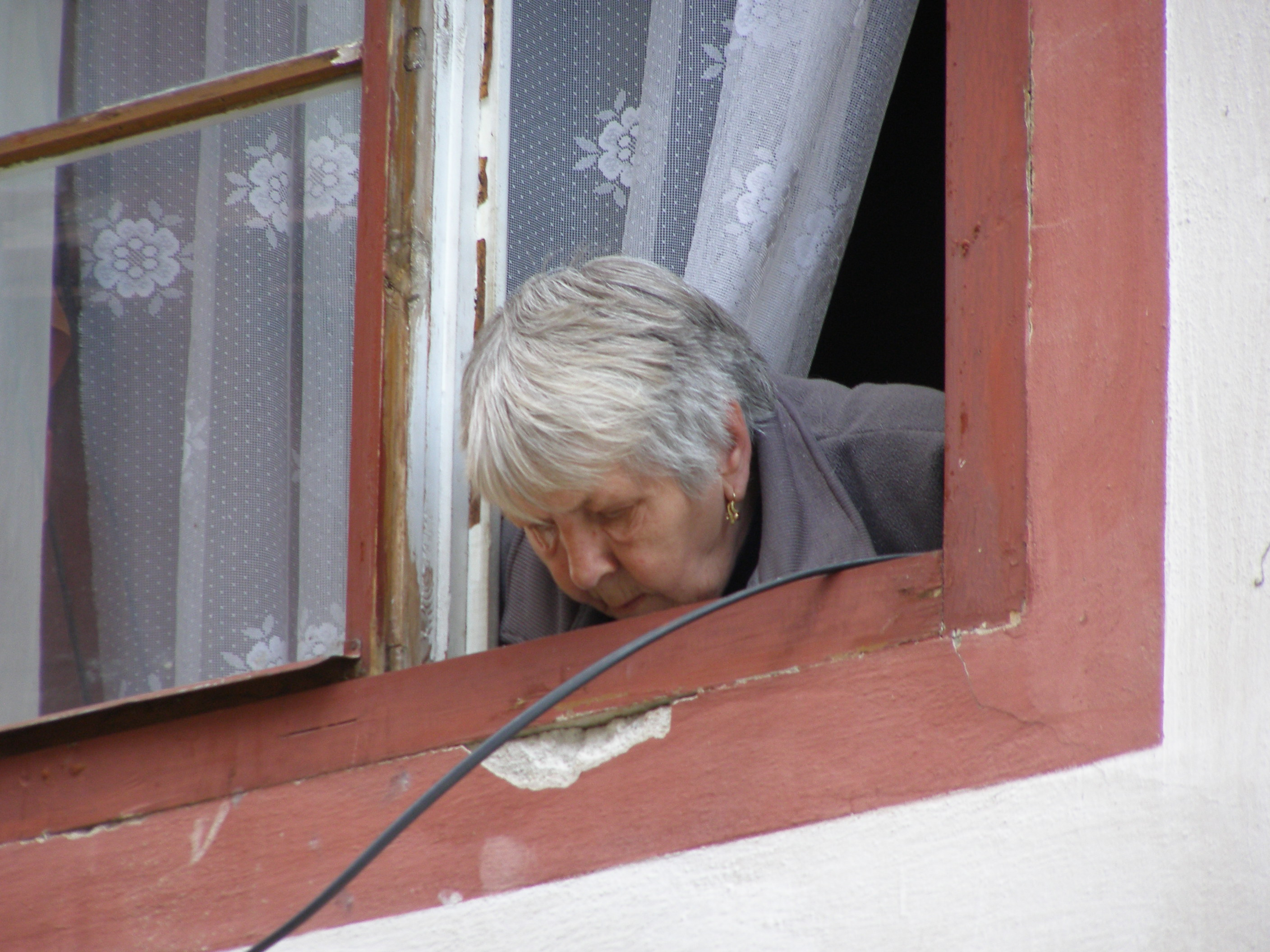 Photo by Erich Ferdinand of an old woman leaning out the window.