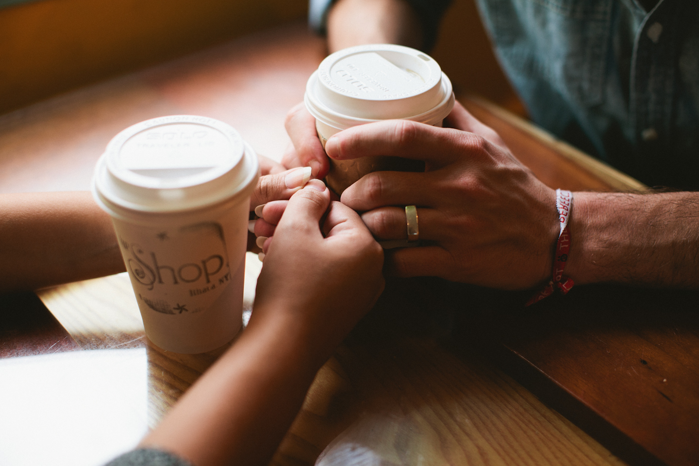 Picture of a two pairs of hands touching while holding cups of coffee