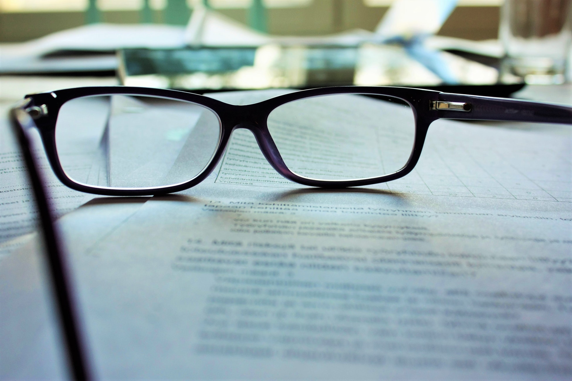 Picture of a pair of black-framed eyeglasses on white printing paper