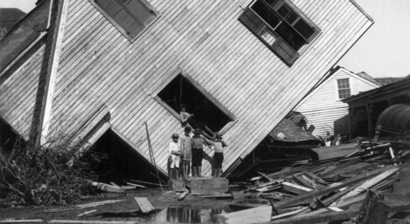 Black and white picture of some boys standing in front of a knocked over house with some other ruins around them.