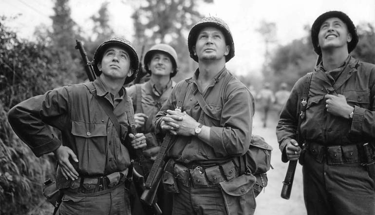 Black and white picture of a group of soldiers looking up into the sky.