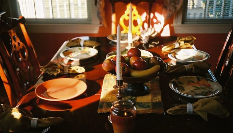 Picture of a set dinner table with candles, a fruit bowl, mantels, and silverware