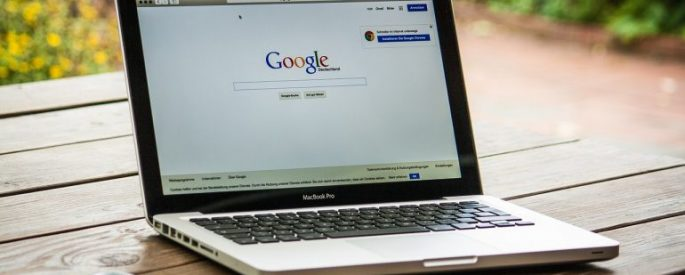 Picture of a laptop screen opened to Google's homepage