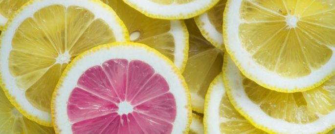A pile of lemon slices, with one grapefruit slice