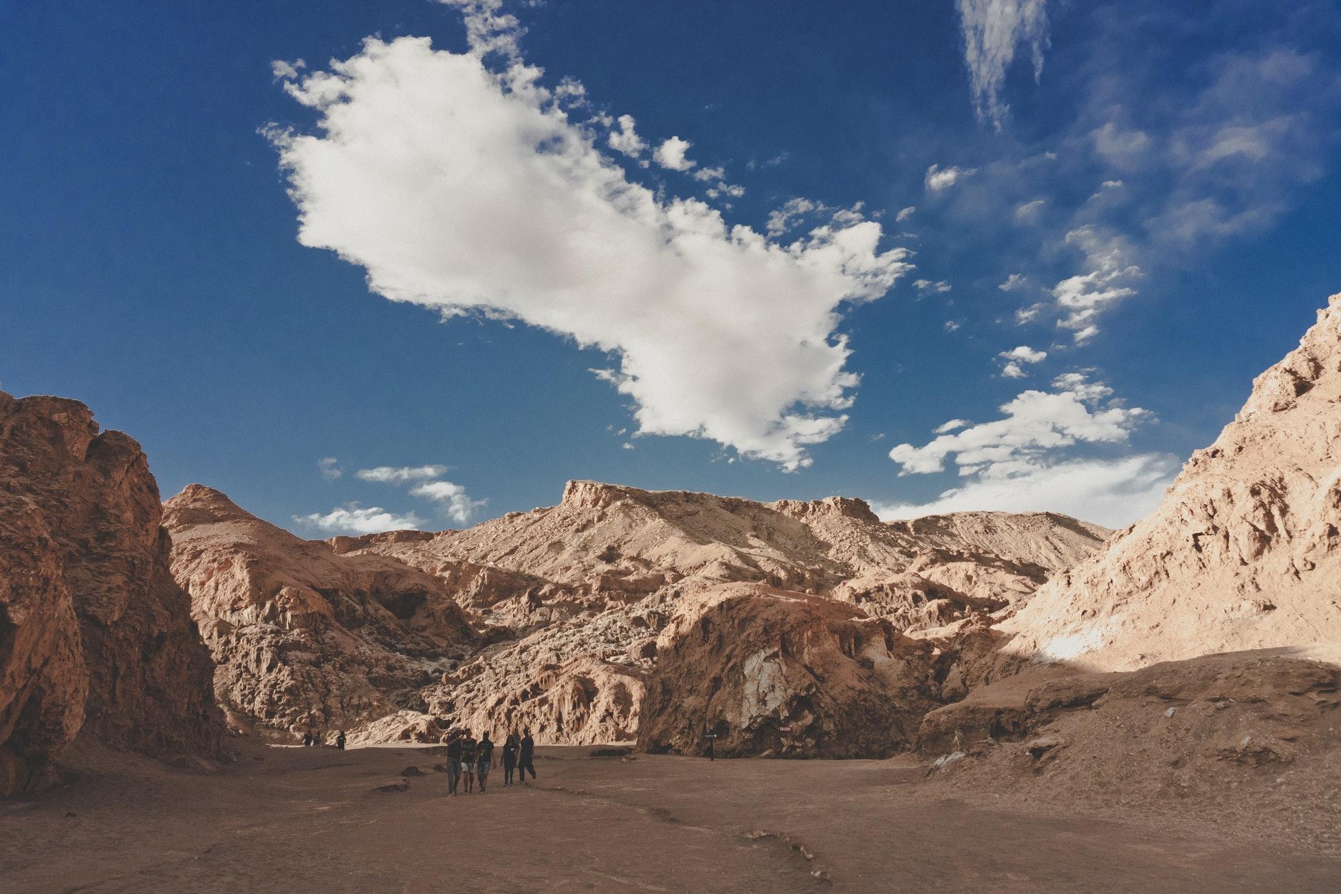 Men walking around in desert under blue sky.