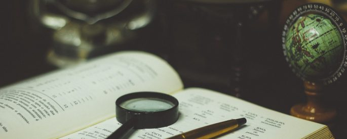 A magnifying glass and pen resting on a book.