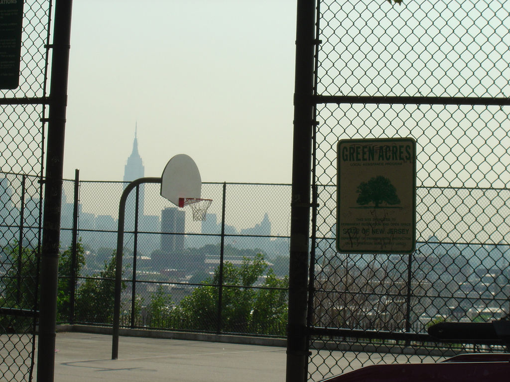 Picture of a basketball court with a city skyline in the background.