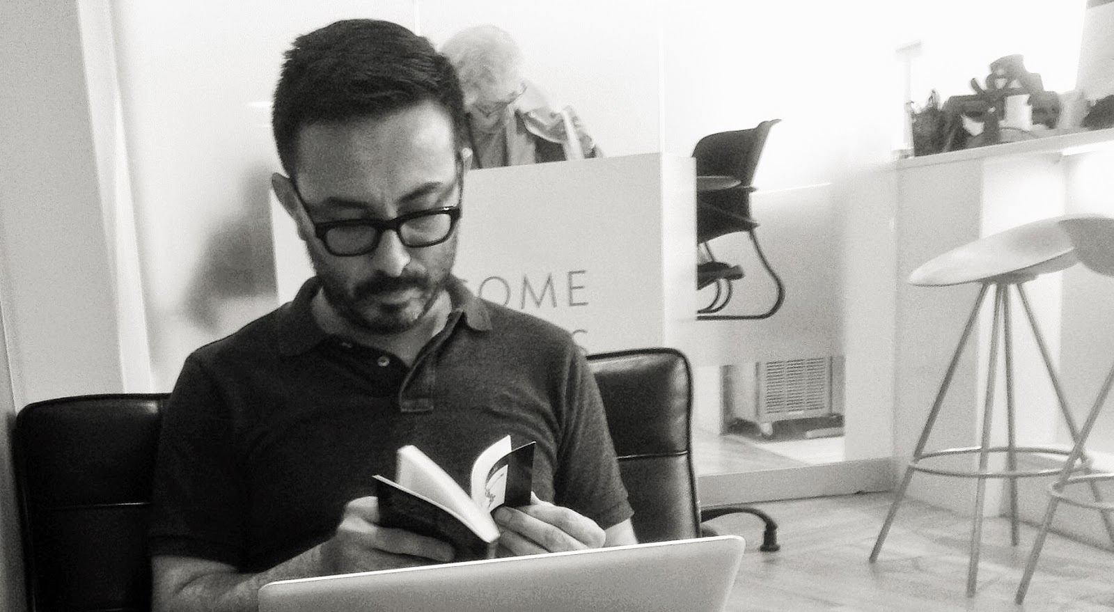 Black and white picture of a man flipping through a notebook.