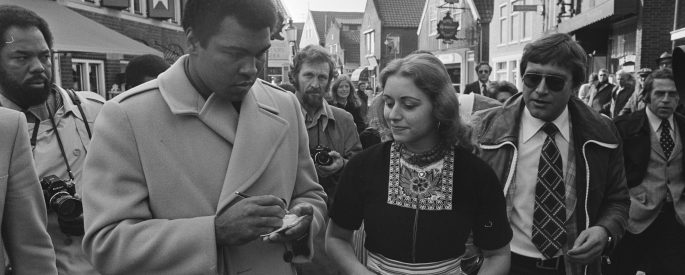 Muhammad Ali signing autographs.
