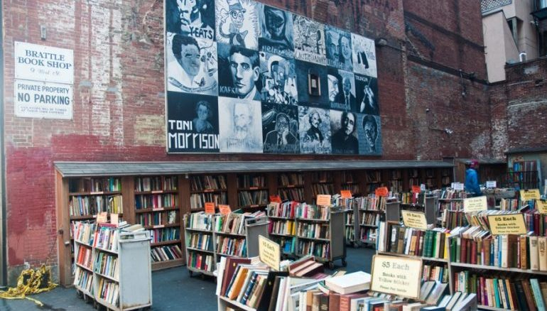 Picture of the Brattle Book Shop in Boston. A lot of bookshelves on the outside of the store.