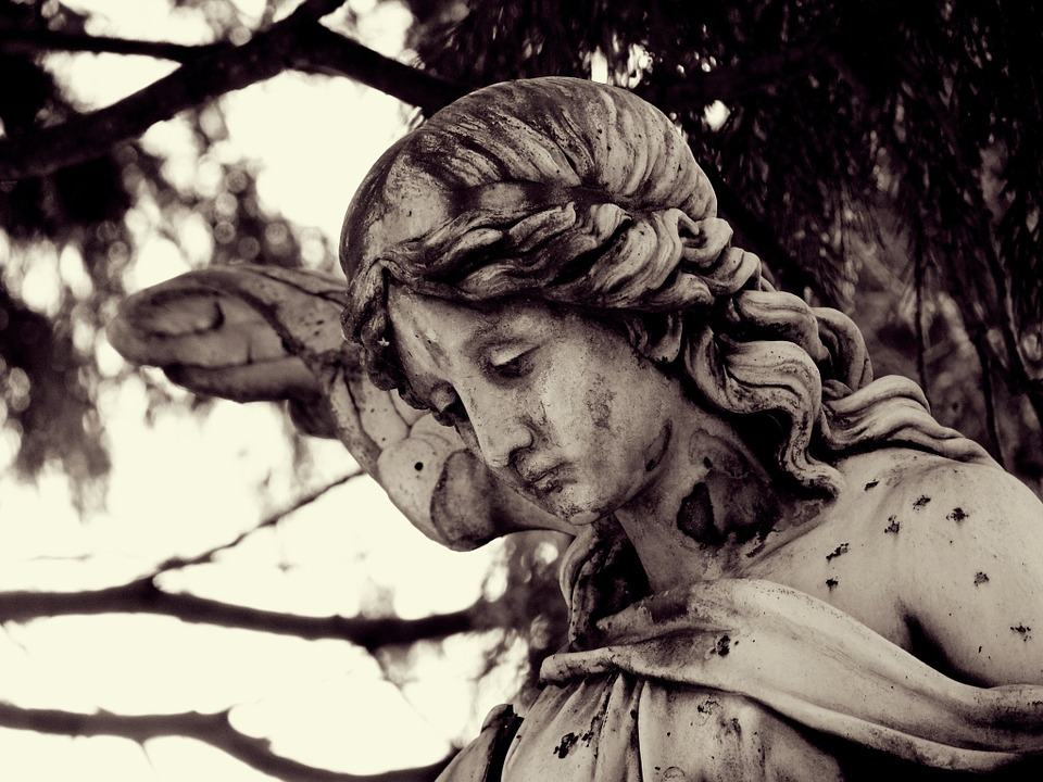 Close up picture of an angel statue with a sad expression.