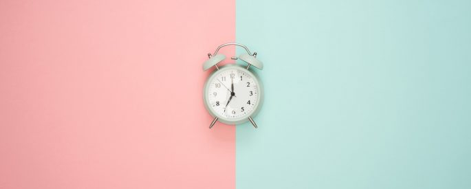 silver bell alarm clock on pink and blue wall