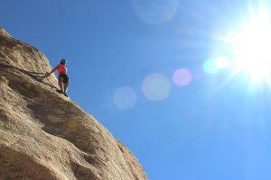 Woman climbing a rock mountain.