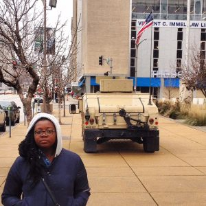 Picture of Jacqui standing with a tank in the background.