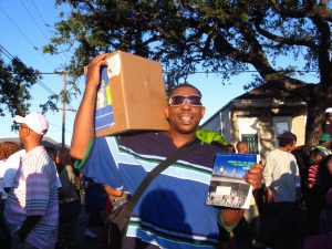 Raphael Parker selling Nine Times books at a second line parade in New Orleans. Photograph by Rachel Breunlin