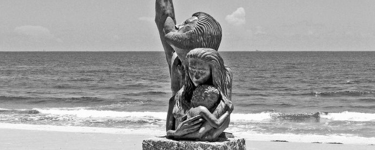 Picture of a statue on a beach of three family members hugging each other