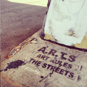 "Picture of the words ""A.R.T.S Art Rules the Streets"" graffitied on the sidewalk"