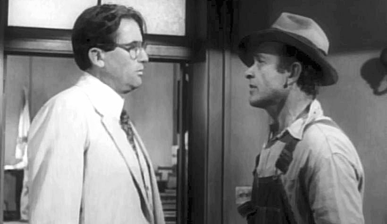 Picture of an old black and white movie, two men facing each other with worried expressions.