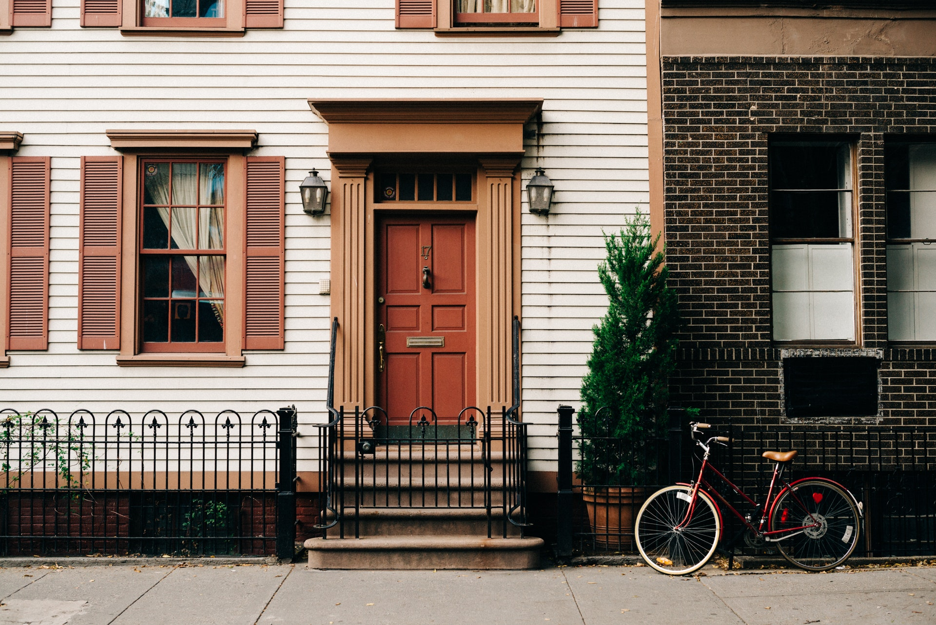 Picture of a house's porch, a bike parked outside.