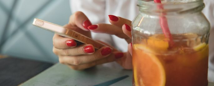 clear glass jar filled with fruit juice woman holding iphone in background.