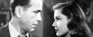 Black and white picture of a man and a woman looking at each other intently.