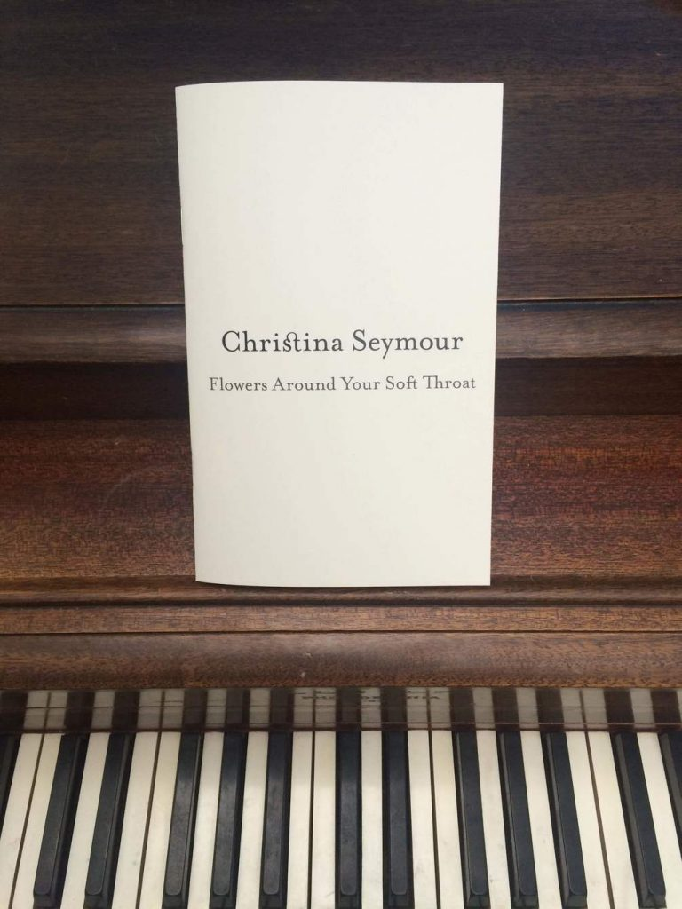 Picture of a Christina Seymour, Flowers Around Your Soft Throat booklet on top of a piano