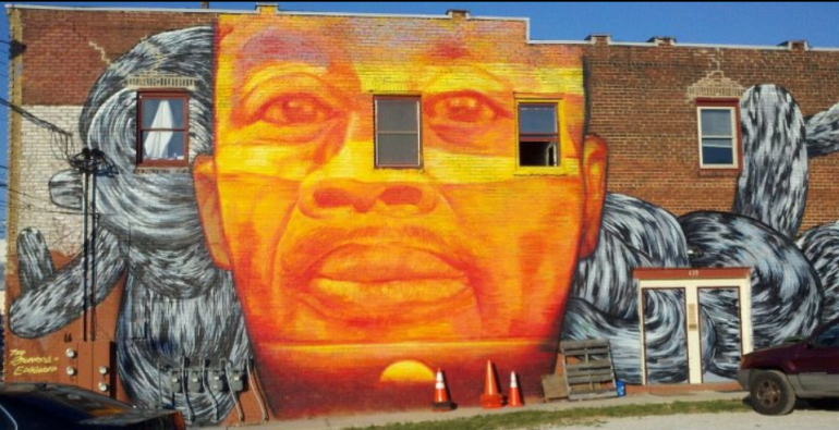 Mural on a brick wall of the face of a Black man.