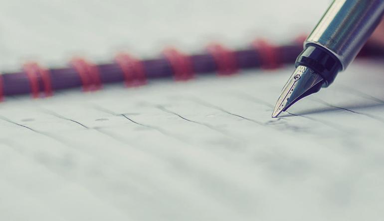A fountain pen writing on a spiral notebook.