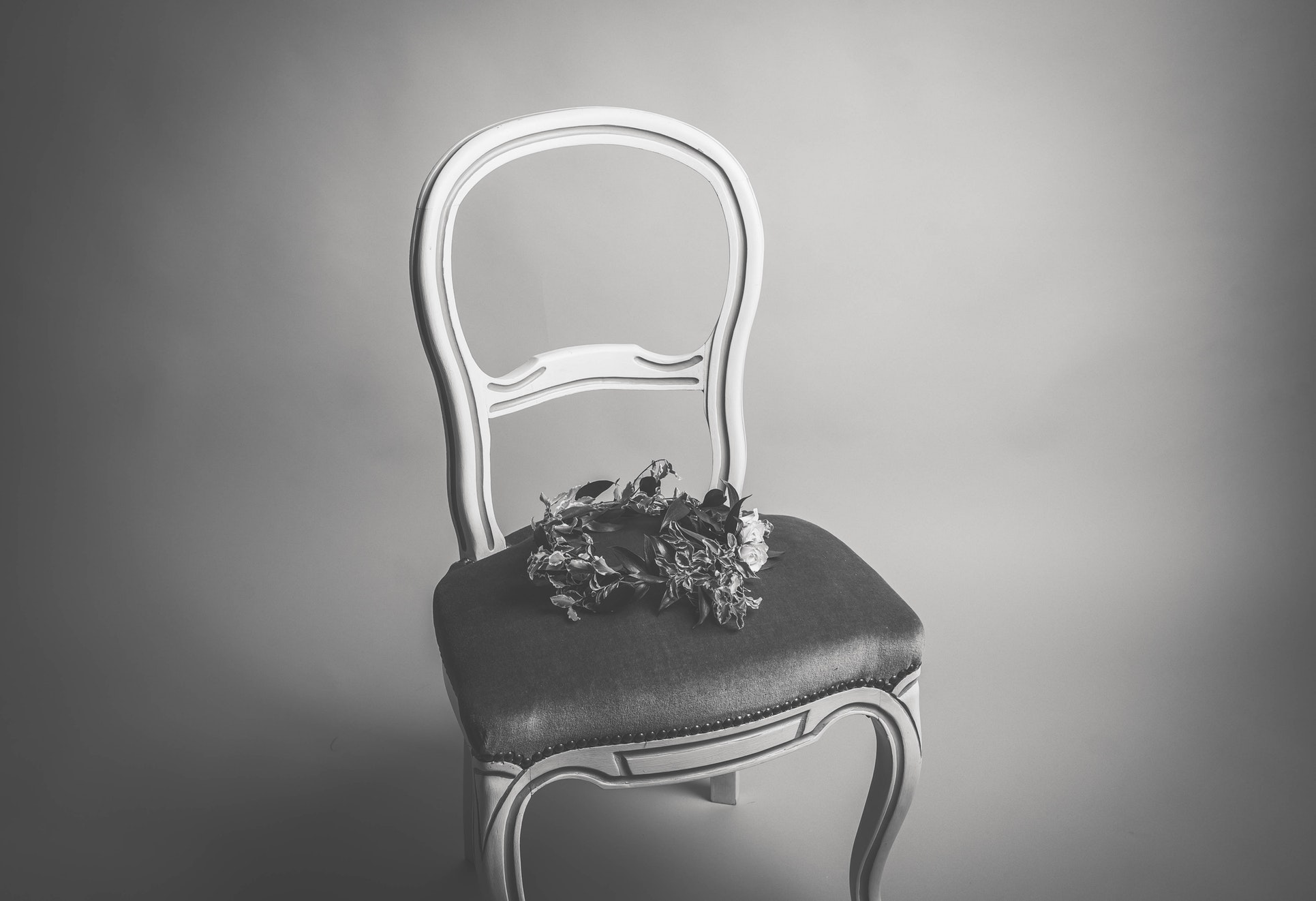 a chair in a dark room with flowers on top of it