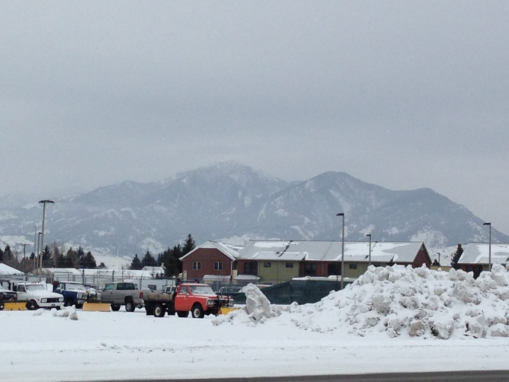 Snowy landscape with trucks parked outside of a building.
