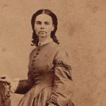 Sepia toned photograph of a woman in a historical dress.