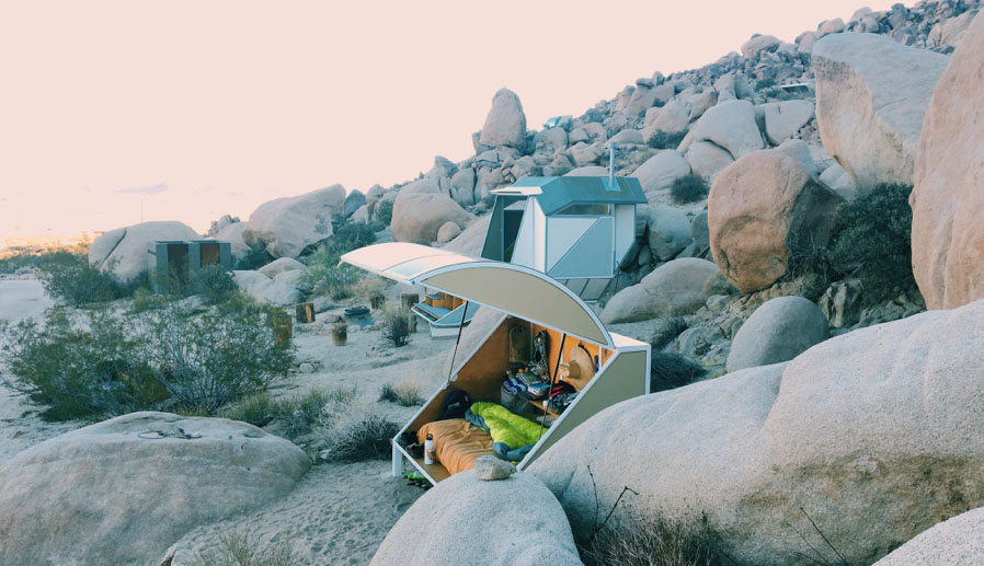 A small camper setup on a rocky hill.