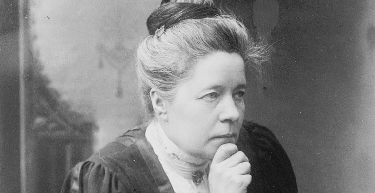 Black and white photo of a woman holding her chin in her hand and looking away from the camera.