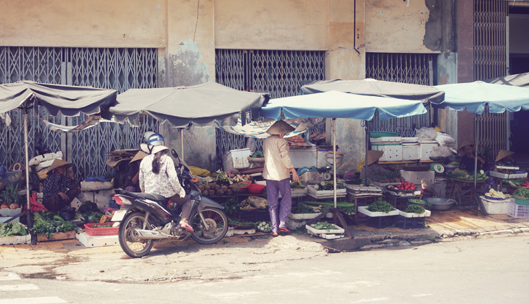 Market stalls for produce with a person on a motorcycle looking at the goods.