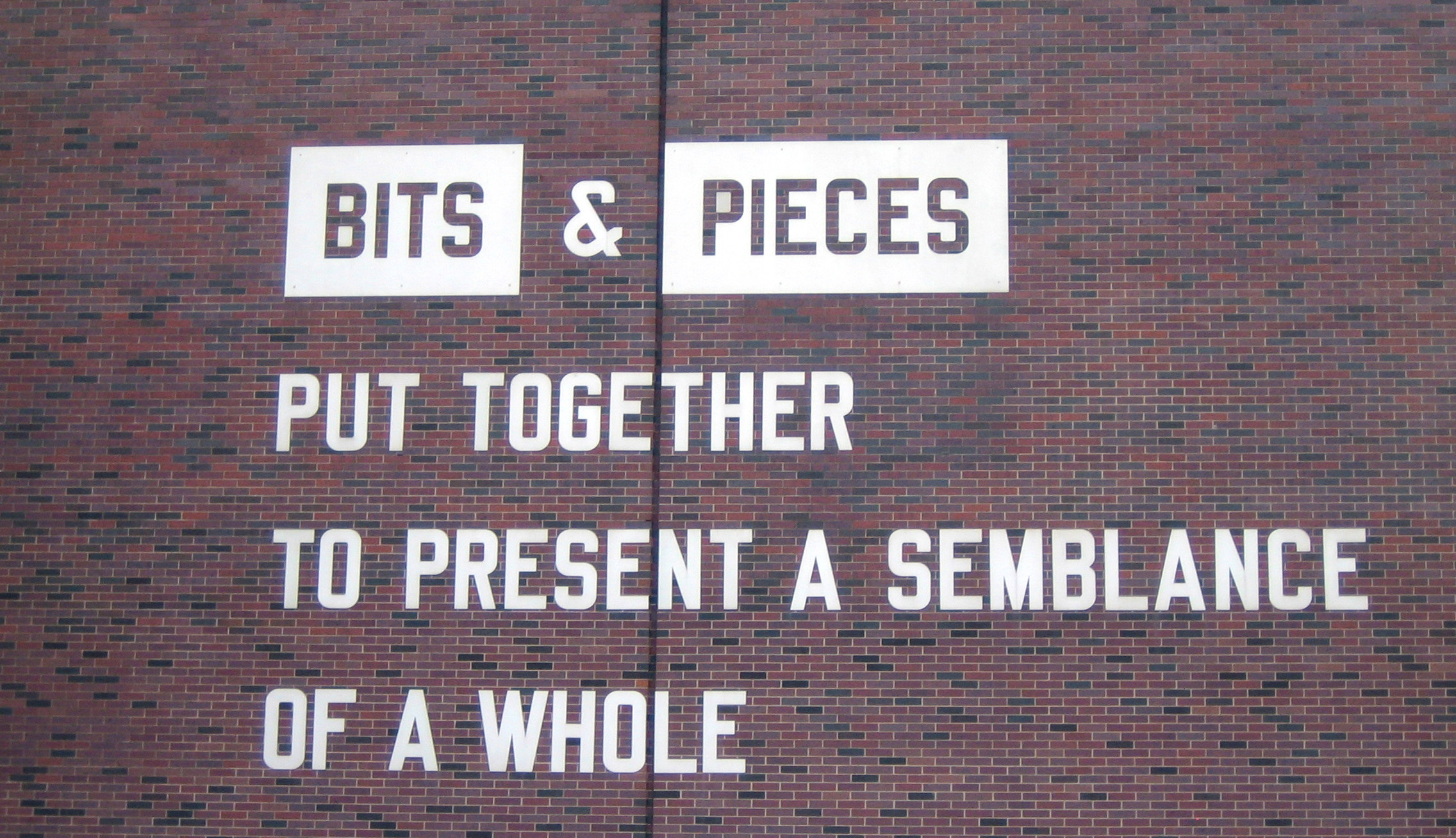 """Brick wall with painted letters that read """"Bits & Pieces put together to present a semblance of a whole."""""""