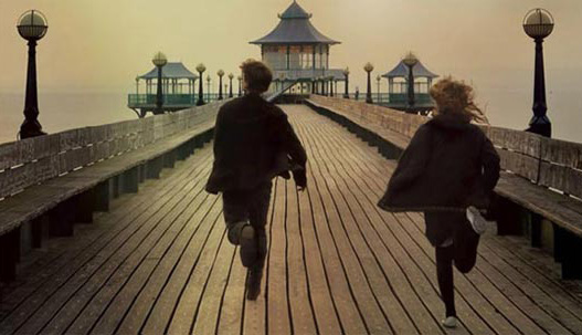 Two people running on a boat dock.