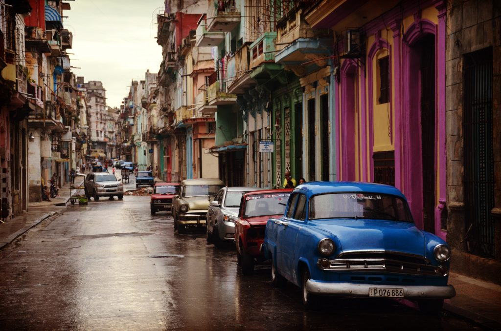 Colorful city street with parked cars on the right side.