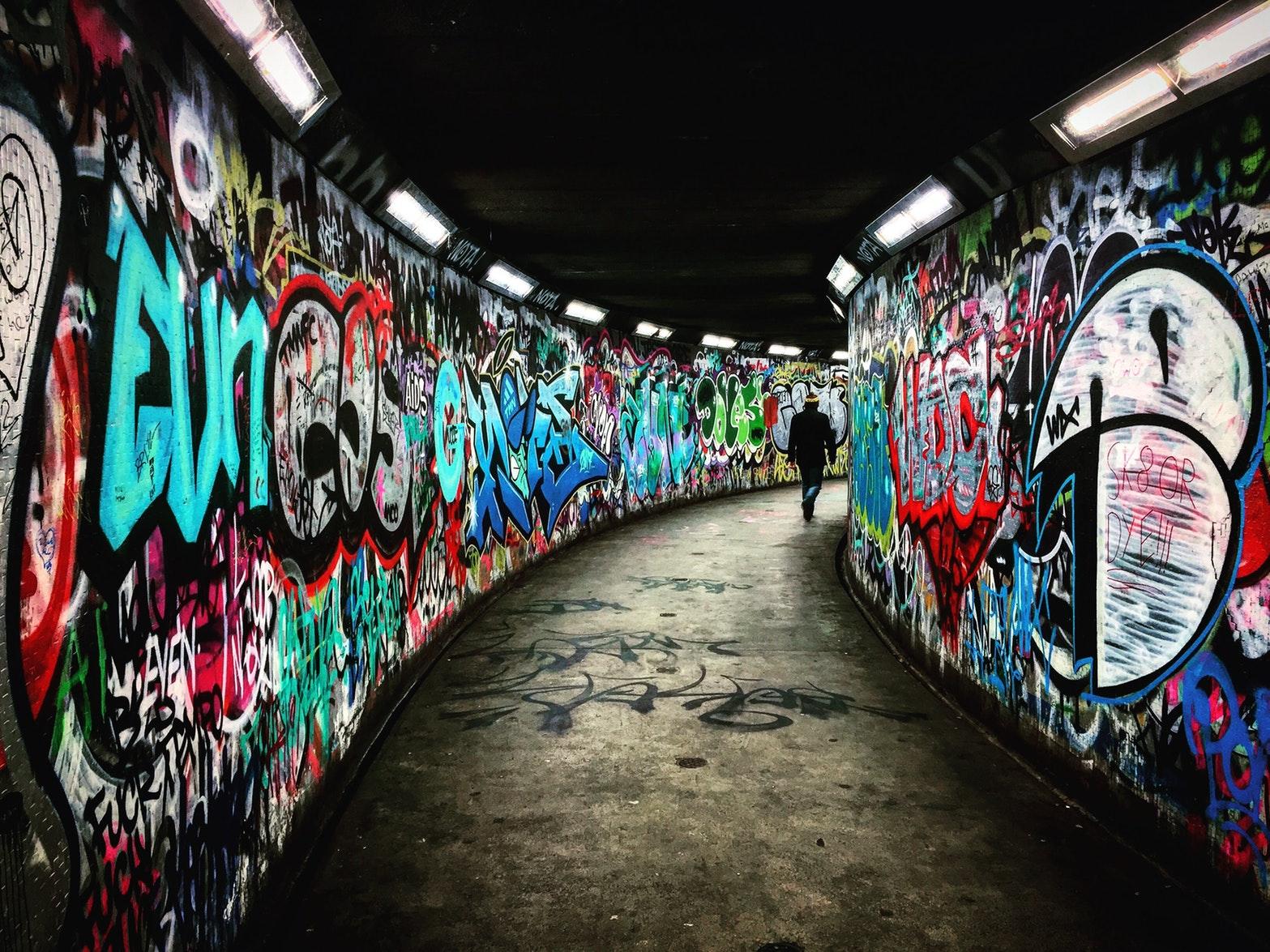 man walking on hallway with graffiti walls