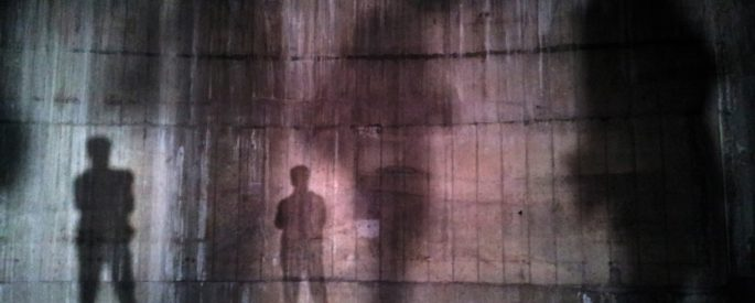 silhouette of man standing near wall on dark area